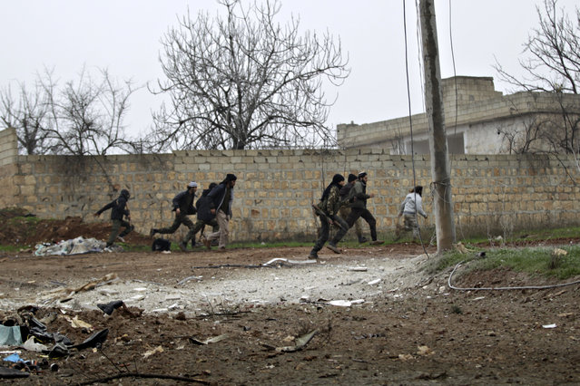 Ahrar al-Sham Islamic fighters run for cover after a fellow fighter was injured from airstrikes around al-Hamidiyeh base, one of two military posts they took control of from forces loyal to Syria's President Bashar al-Assad in the southern Idlib countryside, December 19, 2014. (Photo by Khalil Ashawi/Reuters)