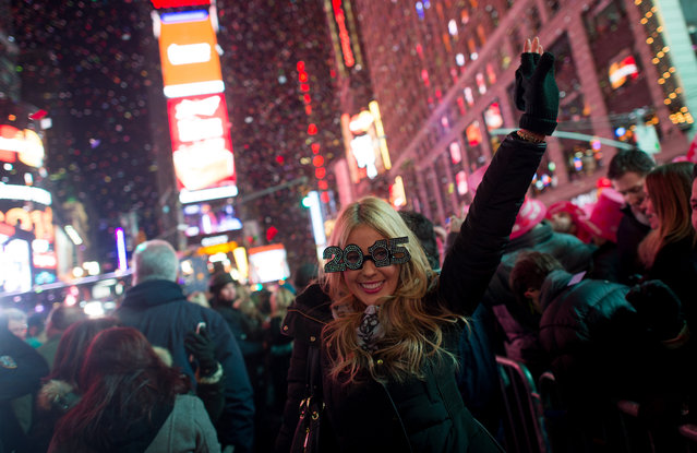 People cheer as the ball drops at midnight in Times Square on January 1, 2015 in New York City. An estimated one million people from around the world are expected to pack Times Square to ring in 2015. (Photo by Andrew Theodorakis/Getty Images)