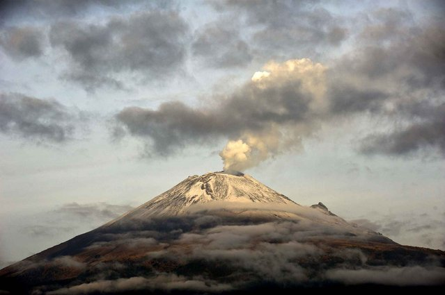"The Popocatepetl Volcano, 55 km southeast of Mexico City, is seen from Santiago Xalitxintla, in Puebla, spewing a cloud of ash and smoke, on May 14, 2013. The National Disaster Prevention Centre raised the alert level on Sunday to ""yellow phase three"". (Photo by Ronaldo Schemidt/AFP Photo)"