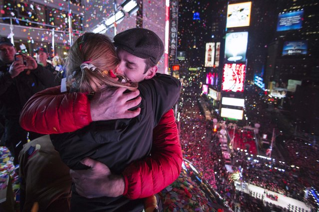 A couple embraces on a balcony amidst confetti after the clock strikes midnight during New Year's Eve celebrations in Times Square, New York January 1, 2015. (Photo by Keith Bedford/Reuters)
