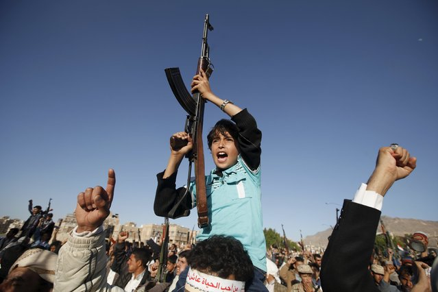 A boy holds up a rifle as he shouts slogans during a demonstration against Saudi-led strikes in Yemen's capital Sanaa November 20, 2015. (Photo by Khaled Abdullah/Reuters)