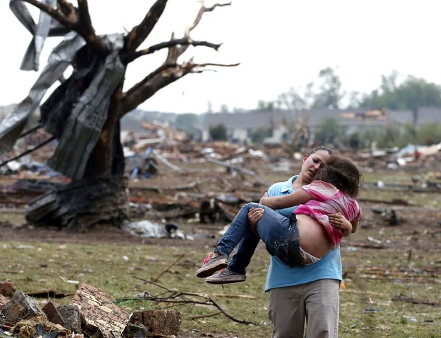 A woman carries a child through a field near the collapsed Plaza Towers Elementary School in Moore, Oklahoma. (Photo by Sue Ogrocki/Associated Press)