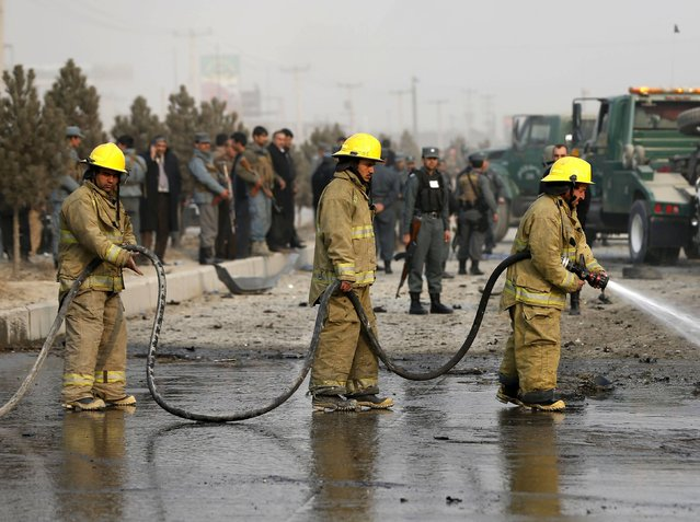 Afghan firefighters spray water to wash the site of a suicide attack in Kabul January 5, 2015. (Photo by Omar Sobhani/Reuters)