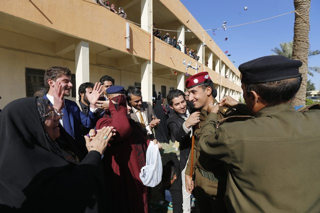 An officer is surrounded by family members as they celebrate at his graduation ceremony during Iraqi Army Day anniversary celebration in Baghdad January 6, 2015. (Photo by Thaier al-Sudani/Reuters)