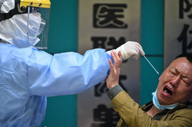 A man being tested for the COVID-19 novel coronavirus reacts as a medical worker takes a swab sample in Wuhan in China's central Hubei province on April 16, 2020. China has largely brought the coronavirus under control within its borders since the outbreak first emerged in the city of Wuhan late last year. (Photo by Hector Retamal/AFP Photo)