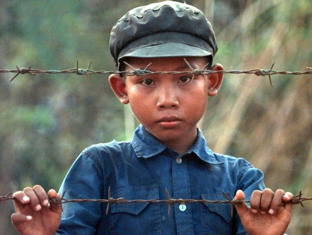 A young Cambodian boy, wearing a Khmer Rouge cap, looks out through barbed wire Sunday, May 3, 1998, at a refugee camp near Huay Samran, Thailand.  Refugees fleeing the fighting between Khmer Rouge and Cambodia forces continue to seek safety in Thailand.  (Photo by David Longstreath/AP Photo)