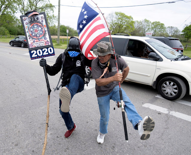 A supporter of U.S. President Donald Trump with the original American Flag designed by Betsy Ross and a Barbie Doll, referencing Michigan Governor Gretchen Whitmer, with a noose around its neck on a fishing pole dances in the street with another supporter wearing a Darth Vader Mask during U.S. President Donald Trumps visit to a Ford Motor Co. plant after it reopened from the coronavirus disease (COVID-19) restrictions in Ypsilanti, Michigan, U.S. May 21, 2020. (Photo by Seth Herald/Reuters)