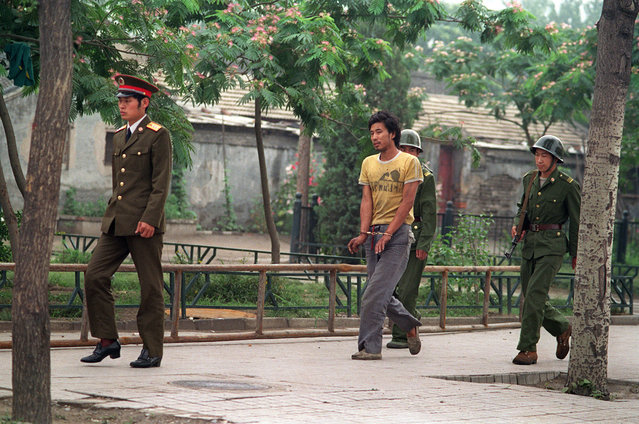 A handcuffed man is led by Chinese soldiers on a street in Beijing, in June of 1989, as police and soldiers searched for people involved in the April-June pro-democracy protests. (Photo by Manuel Ceneta/AFP Photo)