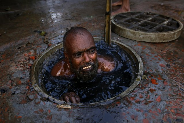 Men are sent down into the sludge to clear the sewers in the Bangladeshi capital Dhaka on May 23, 2018. One man holds his nose as he goes under to scoop blockages out for no more than $10a day. (Photo by Rehman Asad/Barcroft Media)