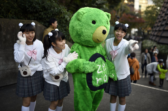 Young Japanese women pose with a green bear costumed person during the 'Earth Parade 2015' in Tokyo, Japan, Saturday, November 28, 2015. (Photo by Franck Robichon/EPA)