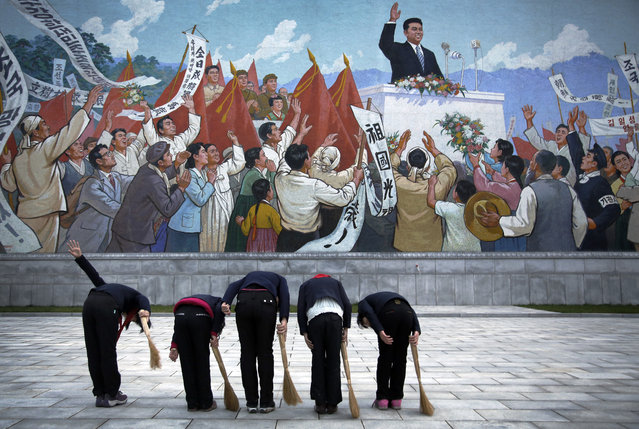 North Korean school girls holding brooms bow to pay their respects toward a mural which shows the late North Korean leader Kim Il Sung delivering a speech, before sweeping the area surrounding this mural on Tuesday, December 1, 2015, in Pyongyang, North Korea. (Photo by Wong Maye-E/AP Photo)