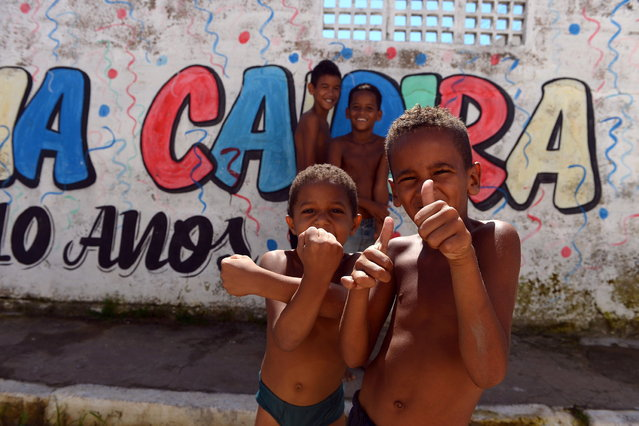 Boys pose for pictures in a shantytown of Olinda, about 18 km from Recife in northeastern Brazil, on June 18, 2013 during the FIFA Confederations Cup Brazil 2013 football tournament. The historic centre of Olinda is listed as an UNESCO World Heritage Site. (Photo by Vincenzo Pinto/AFP Photo)