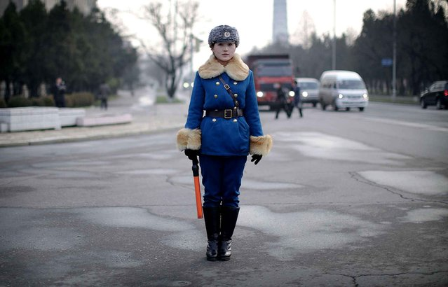A North Korean traffic police woman directs vehicles at an intersection on Wednesday, December 2, 2015, in Pyongyang, North Korea as residents commute at the end of a work day. (Photo by Wong Maye-E/AP Photo)