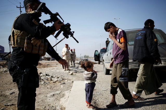 A girl who just fled Samah district of eastern  Mosul stands with a relative as she arrives at Iraqi Special Forces checkpoint in Kokjali, east of Mosul, Iraq November 5, 2016. (Photo by Zohra Bensemra/Reuters)
