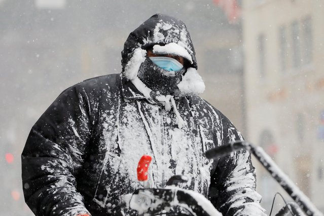 A worker covered in snow clears a street during a snow storm, amid the coronavirus disease (COVID-19) outbreak, in the Manhattan borough of New York City, New York, U.S., February 1, 2021. (Photo by Andrew Kelly/Reuters)