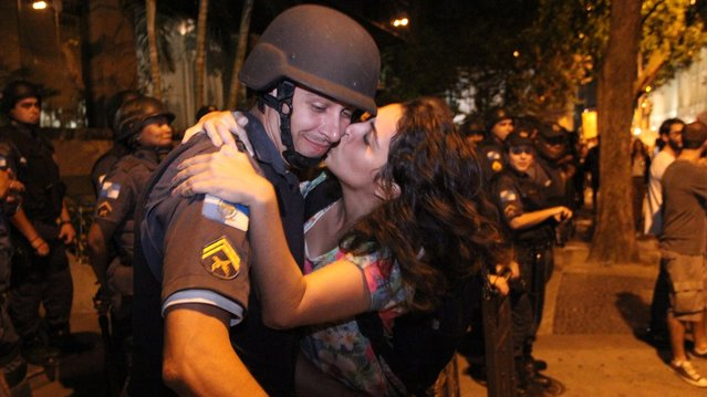 The student Patricia Vasconcellos de Almeida, 22, tried to kiss one of the military police who formed a cordon ostensibly in front of the building Fetranspor (Federation of Transport Companies), in Rio de Janeiro, on June 27, 2013. (Photo by Zulmair Rocha/UOL)