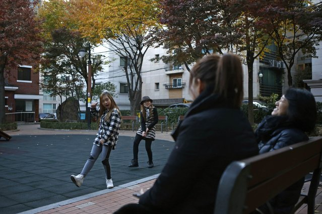 Kim Si-yoon and Yoo Ga-eul (L) dance in front of their mothers as they play at a playground in Seoul November 15, 2014. (Photo by Kim Hong-Ji/Reuters)