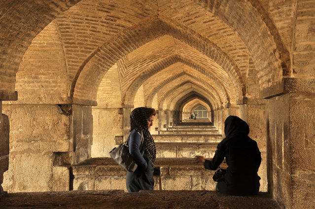 """Women in Kaju Bridge"". This photo is taken in Esfahan, Iran in Kaju bridge. The look of one women with attractive eyes to her friend in front of the graphics of the bridge took my attention. (Photo and caption by Murat Bergi/National Geographic Traveler Photo Contest)"