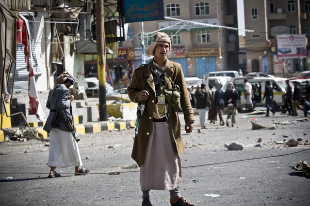 """Houthi Shiite Yemeni gather while guarding a street leading to the presidential palace in Sanaa, Yemen, Tuesday, January 20, 2015. Yemen's U.S.-backed leadership came under serious threat Monday as government troops clashed with Shiite rebels near the presidential palace and a key military base in what one official called """"a step toward a coup"""". (Photo by Hani Mohammed/AP Photo)"""