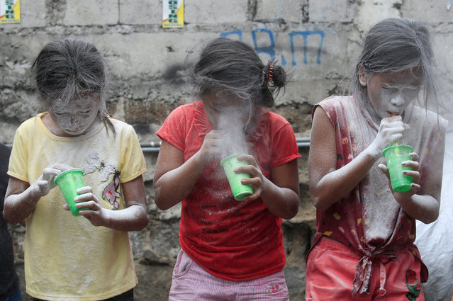 Girls' faces are covered by white powder after blowing it, at a town fiesta parlour game, in celebration of patron saint Santa Rita de Cascia in Baclaran, Paranaque City, Metro Manila, Philippines May 20, 2018. (Photo by Romeo Ranoco/Reuters)