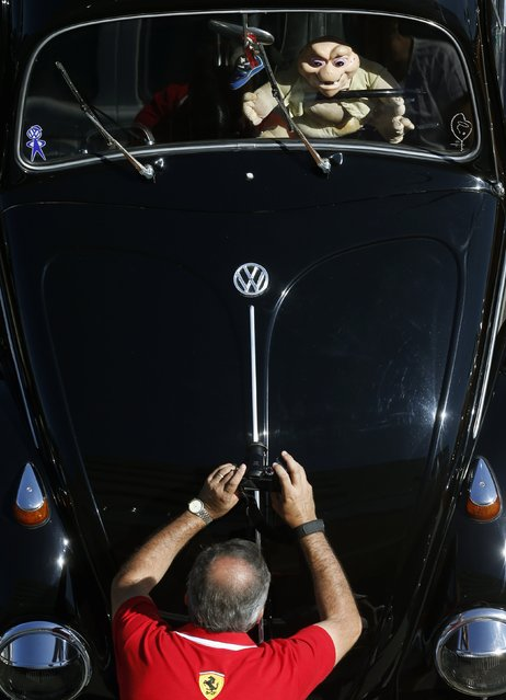 A visitor takes a photograph during a Volkswagen Beetle owners' meeting in Sao Bernardo do Campo January 25, 2015. (Photo by Paulo Whitaker/Reuters)