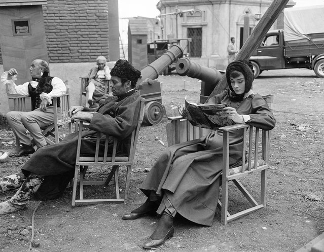 "Decked out in 19th century Russian regalia, film stars Audrey Hepburn and Henry Fonda relax to their individual tastes on the set of ""War And Peace"", in Rome, Italy on September 7, 1955. Miss Hepburn scans a magazine while Fonda grabs 40 winks. The celluloid version of the Tolstoi novel is reportedly a five million dollar production. (Photo by AP Photo)"
