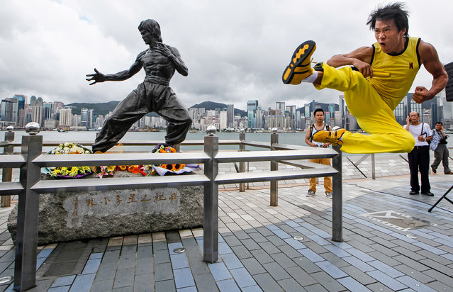 "Chinese actor Mei Zhiyong dressing as the late Hong Kong Kung Fu star Bruce Lee performs in front of the bronze statue in Hong Kong Saturday, July 20, 2013 to commemorate the 40th anniversary of the death of Lee. The late superstar Bruce Lee is best-known for the kung fu skills he displayed in his movies, but his daughter hopes that more people take the effort to understand his teachings and life philosophy. Marking his death 40 years ago on July 20, the Hong Kong government has teamed up with the Bruce Lee Foundation to put together an exhibition to showcase the late star's life, from his famous yellow tracksuit he wore in the movie ""Game of Death"", to his writings and drawings. (Photo by Kin Cheung/AP Photo)"