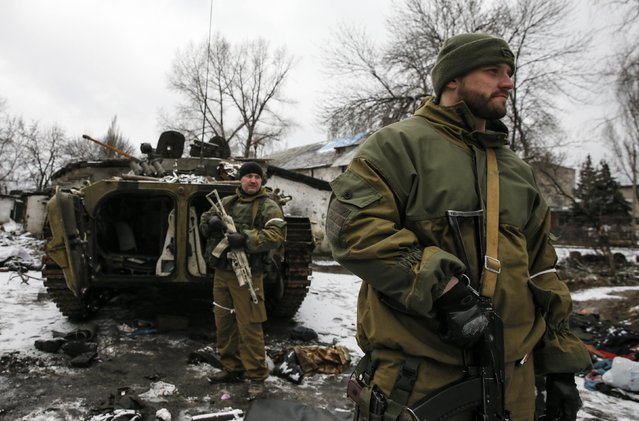 Members of the armed forces of the separatist self-proclaimed Donetsk People's Republic gather near an armoured vehicle destroyed during battles with the Ukrainian armed forces in Vuhlehirsk, Donetsk region, February 4, 2015. (Photo by Maxim Shemetov/Reuters)