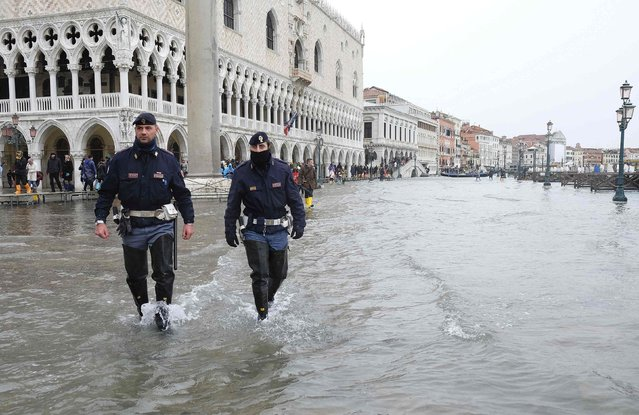 Policemen patrol a flooded St. Mark's Square during a period of seasonal high water in Venice, February 6, 2015. (Photo by Manuel Silvestri/Reuters)