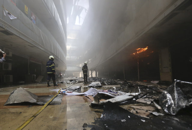 Firefighters work to control a fire at a Sunrise Hospital, a private hospital treating coronavirus patients, in India's financial capital of Mumbai, Friday, March 26, 2021. The fire killed at least 10 people and more than 70 patients were evacuated to other hospitals in the city. Firefighting crews were still working to control the blaze, which broke out early Friday, with 20 fire engines and ambulances at the scene, said an official at the fire services control room. (Photo by Emmanual Yogini/AP Photo)