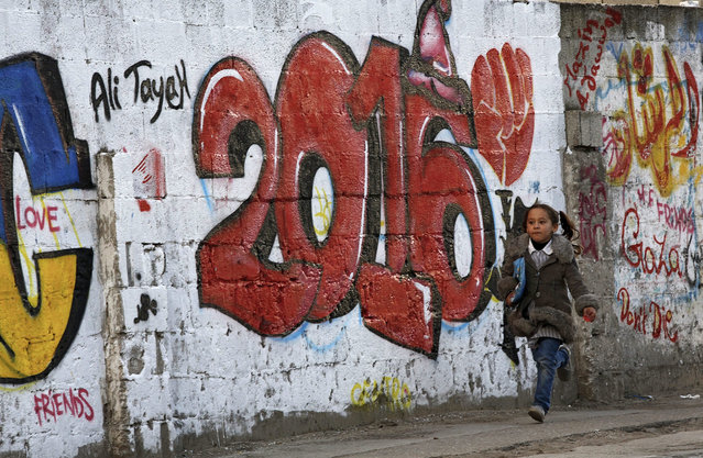 """A Palestinian girl runs past a graffiti reading the new year """"2016"""" as she returns to her house after school in Gaza City, 30 December 2015. According to reports, the graffiti were painted by Italian artists. Police in the Gaza Strip announced on 30 December that New Year's celebrations in the coastal enclave are banned as a contradiction of Islam. (Photo by Mohammed Saber/EPA)"""