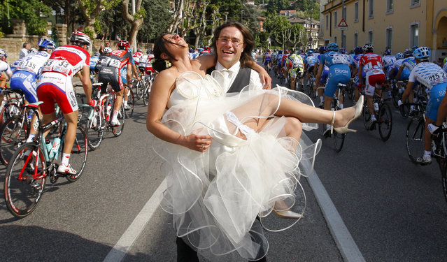 A newly-wed couple pose as cyclists ride past during the second stage from Jesolo to Trieste of the Giro d'Italia, May 10, 2009. Italy's Alessandro Petacchi won the stage while Britain's Mark Cavendish took the leader's pink jersey. (Photo by Stefano Rellandini/Reuters)