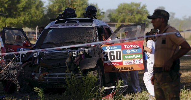 Mini driver Guo Meiling of China (inside the car) receives medical attention after she had an accident during the Buenos Aires-Rosario prologue stage of Dakar Rally 2016 in Arrecifes, Argentina, January 2, 2016. (Photo by Marcos Brindicci/Reuters)