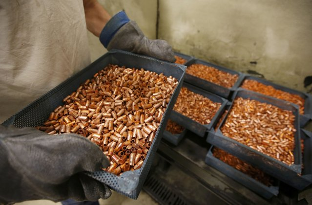 A worker transfers newly made copper slugs, to be pressed into bullets, at Barnes Bullets in Mona, Utah, January 6, 2015. (Photo by George Frey/Reuters)