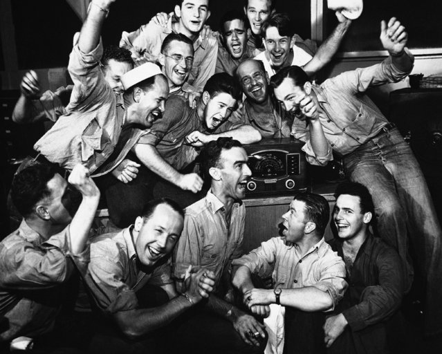 Sailors in the disbursing storekeepers department of Navy in Pearl Harbor, Hawaii on August 17, 1945, listen to radio and cheer as Tokyo radio states Japan has accepted Potsdam surrender terms on August 13. (Photo by AP Photo)