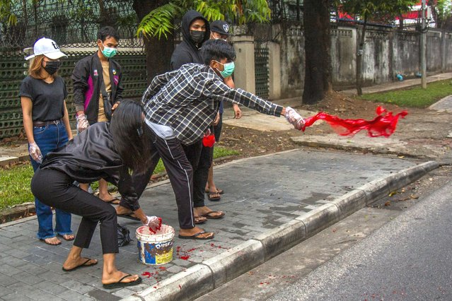 Anti-coup protesters throw red paint on a street during a demonstration in Yangon, Myanmar, Tuesday April 6, 2021. Threats of lethal violence and arrests of protesters have failed to suppress daily demonstrations across Myanmar demanding the military step down and reinstate the democratically elected government. (Photo by AP Photo/Stringer)