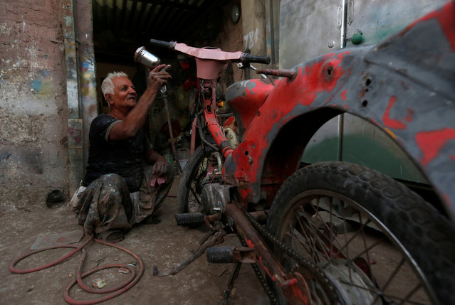 Mohammad Ibrahim uses a spray gun to paint on an old motorbike at his workshop in a low income residential area in Karachi, Pakistan, November 15, 2016. (Photo by Akhtar Soomro/Reuters)