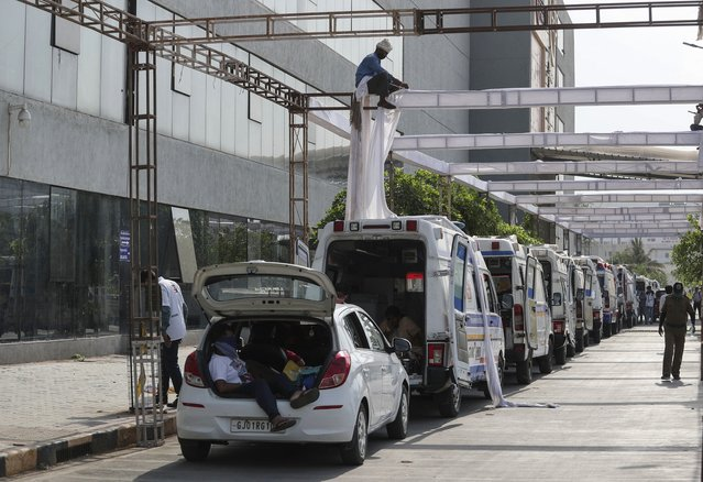 Ambulances carrying COVID-19 patients wait for their turn to be attended out side a government COVID-19 hospital as a worker erects a sun shade in Ahmedabad, India, Tuesday, April 27, 2021. (Photo by Ajit Solanki/AP Photo)