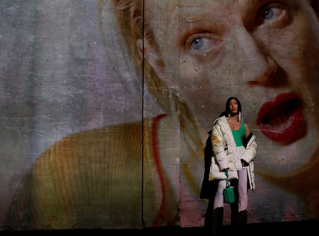 A guest poses against a video installation displayed at the Moncler catwalk show during Milan Fashion Week Spring 2019 in Milan, Italy, September 19, 2018. (Photo by Stefano Rellandini/Reuters)