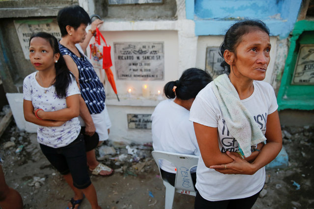 The mother and sister of Angelo Lafuente, whose body, riddled with bullets, was found by a filthy river that feeds into the Manila bay, visit his grave on the All Saints Day in Manila, Philippines November 1, 2016. (Photo by Damir Sagolj/Reuters)