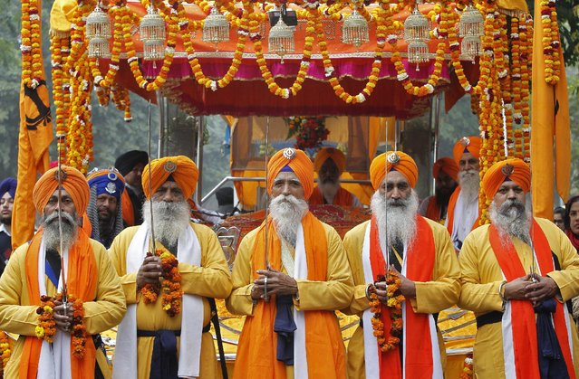 "Sikhs dressed as ""Panj Pyaare"", or the five beloved of Sikh Gurus, hold swords as they take part in a religious procession ahead of the birth anniversary of Guru Gobind Singh in Chandigarh, India, January 14, 2016. Guru Gobind Singh was the last and the tenth Guru of the Sikhs. (Photo by Ajay Verma/Reuters)"