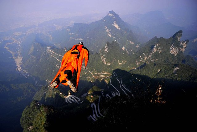 Hungarian wingsuit flier Viktor Kovats jumps off a mountain at Tianmen Mountain National Forest Park in Zhangjiajie, China, on Oktober 9, 2013. Kovats died during this fatal jump into a gorge. His body was recovered Wednesday from the steep, forested valley floor at the park, state broadcaster CCTV said. The reports said the highly experienced Kovats apparently died from a head injury after crashing into a cliff-side. His 2,290-foot jump was part of preparations for the Second World Wingsuit Championship being held in the park from October 11 to 13. (Photo by Associated Press)