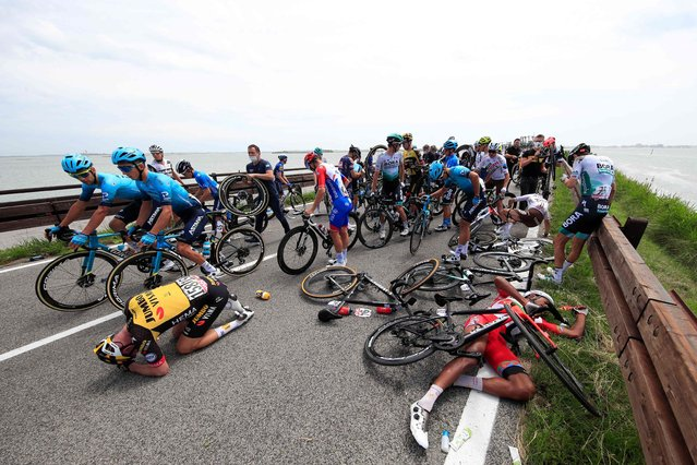 Riders react after a massive pack crash during the 15th stage of the Giro d'Italia 2021 cycling race, a 147km race between Grado and Gorizia on May 23, 2021. (Photo by Luca Bettini/AFP Photo)