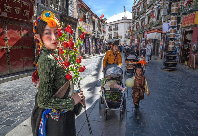A woman has her photo taken wearing tradtional clothing as a Tibetan Buddhist woman and her family walk the kora near the Jokhang Temple, a UNESCO heritage site, during a government organized visit for journalists on June 1, 2021 in Lhasa, Tibet Autonomous Region, China. (Photo by Kevin Frayer/Getty Images)