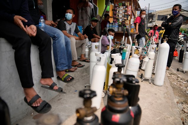 People queue up to refill their oxygen tanks at a filling station in Jakarta, Indonesia, Monday, July 5, 2021. Parts of Indonesia lack oxygen supplies as the number of critically ill COVID-19 patients who need it increases, the nation's pandemic response leader said Monday, after dozens of sick people died at a public hospital that ran out of its central supply. (Photo by Dita Alangkara/AP Photo)