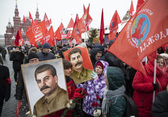 Communist supporters hold portraits of Soviet leader Josef Stalin as they queue to lay flowers at the grave of Stalin to mark the 139th anniversary of his birth, in Moscow's Red Square, Russia, Friday, December 21, 2018. (Photo by Pavel Golovkin/AP Photo)