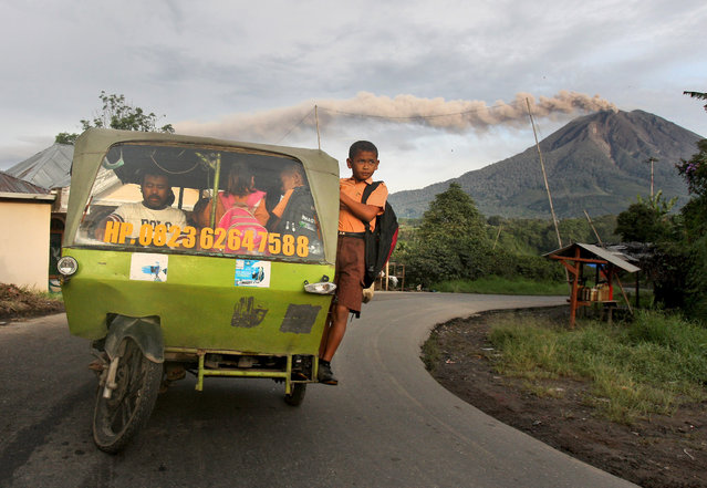Elementary schoolchildren ride on a tricycle on their way to school as Mount Sinabung spews volcanic ash into the air, in Tiga Pancur, North Sumatra, Indonesia, Friday, November 29, 2013. Authorities raised the alert status of the volcano to the highest level on Sunday after it had a series of eruptions. (Photo by Binsar Bakkara/AP Photo)