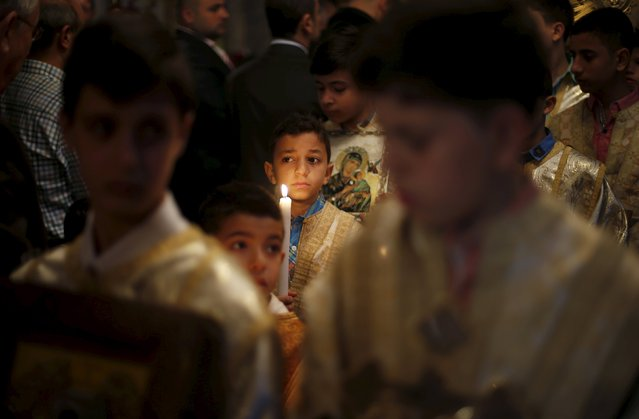 A Palestinian boy holds a candle as he attends Orthodox Christian Palm Sunday mass at the Saint Porfirios church in Gaza City April 5, 2015. (Photo by Suhaib Salem/Reuters)