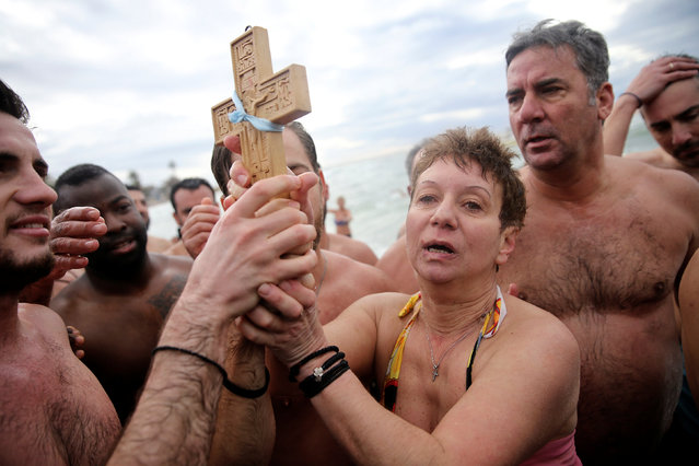 Orthodox faithful hold a wooden crucifix during Epiphany day celebrations in the southern suburb of Faliro in Athens, Greece January 6, 2017. (Photo by Alkis Konstantinidis/Reuters)