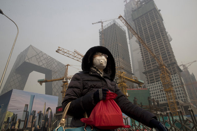 A woman wears a mask as she walks past a construction site as smog continues to choke Beijing on Friday, January 6, 2017. The official Xinhua News Agency reported this week that the environmental ministry had given out punishments after finding that more than 500 construction sites and enterprises, including metallurgy, agricultural chemical and steel plants, and 10,000 vehicles had breached pollution response plans. (Photo by Ng Han Guan/AP Photo)